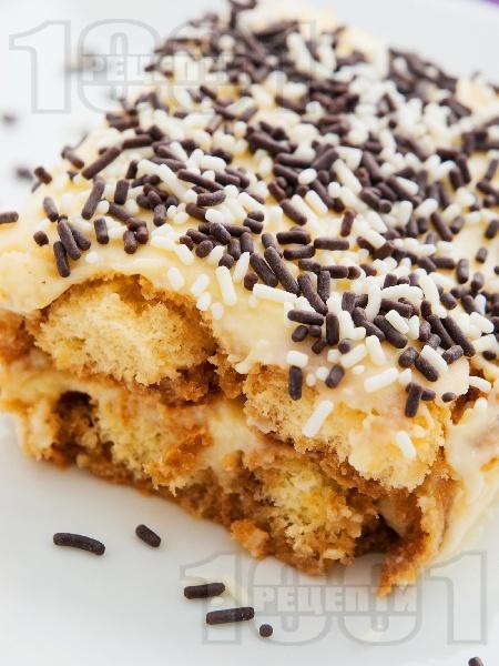 Домашна бишкотена торта с ванилов крем от мляко и сладкарска сметана декорирана с шоколадови пръчици - снимка на рецептата